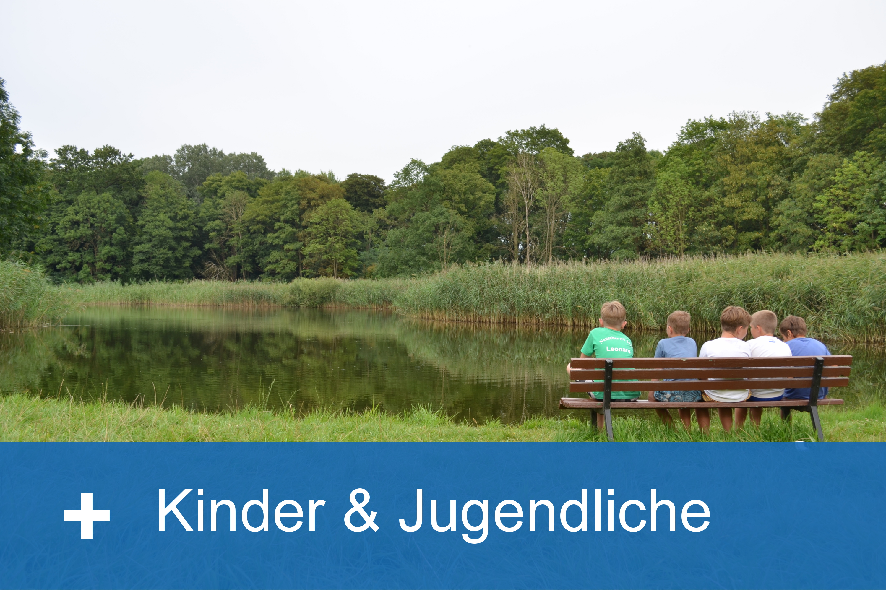 Kinder sitzen auf einer Bank am See