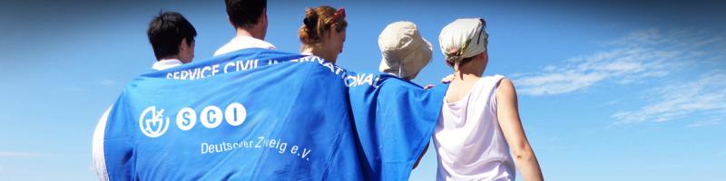 Menschen mit der Flagge des Service Civil International